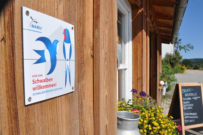 """Plakette """"Schwalbenfreundliches Haus"""" am Hofladen - Foto: Stefan Bosch"""